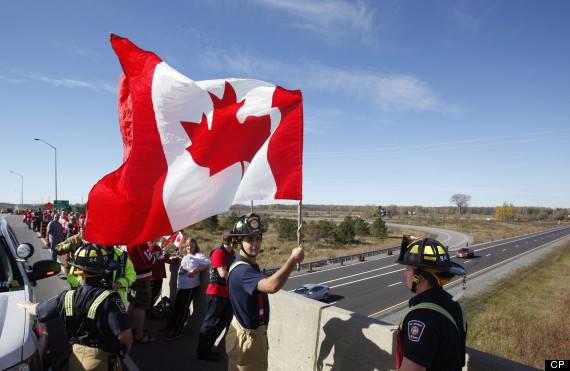 An Ottawa firefighter waves a Canadian Flag as crowds wait on an overpass at the Veterans Memorial Highway for a procession transporting the body of Cpl. Nathan Cirillo to pass by in Ottawa on Friday, October 24, 2014. THE CANADIAN PRESS/ Patrick Doyle